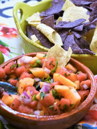 clay mexican style bowl of watermelon and cantaloupe salsa along side a lime colored ceramic handled bowl of blue and white tortilla chips on a rose floral napkin on a wood platter