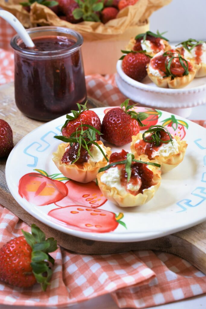 a strawberry printed ceramic plate with phyllo cups filled with cream cheese with red pepper strawberry jam drizzled on top of each one with chopped basil as garnish on top of cutting board