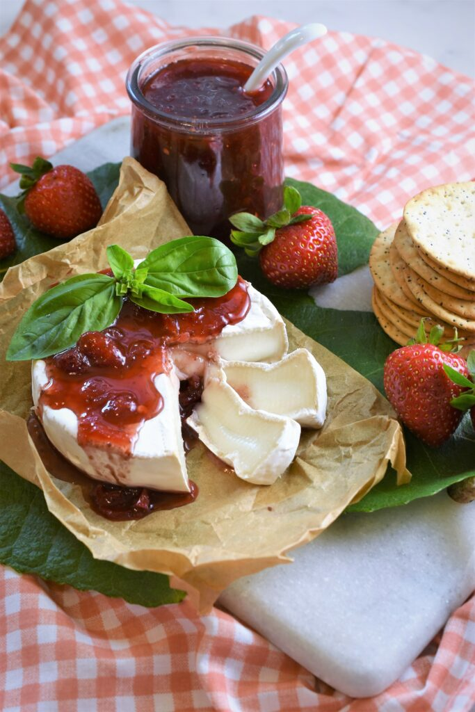 a cut wheel of Brie on parchment paper on marble cutting board with jam poured on top along side of a stack of crackers with strawberries and an open jar of jam