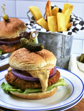up close image of 1 Chipotle Butternut Squash Burger with others in the background with Hatch Chile Aioli on a blue and white plate with french fries in galvanized steel cup
